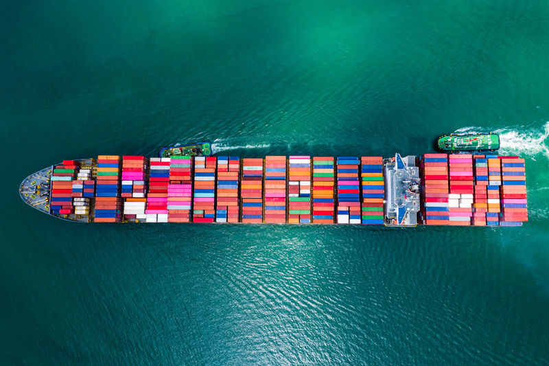 High angle view of container ship import export international sailing in green sea