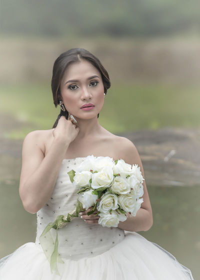Portrait Of Beautiful Bride Holding White Roses Bouquet