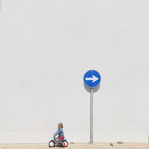 Girl Riding Tricycle Against Arrow Symbol By Wall