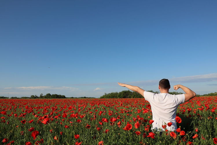 Rear view of person standing on field against blue sky