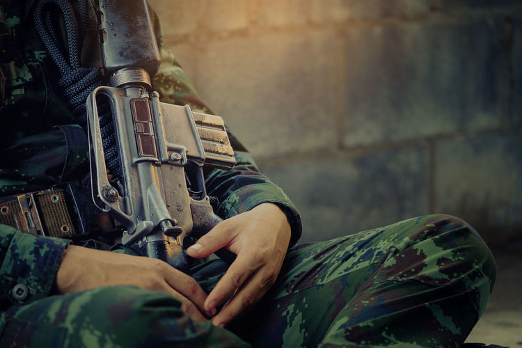 Midsection of army soldier sitting with weapon