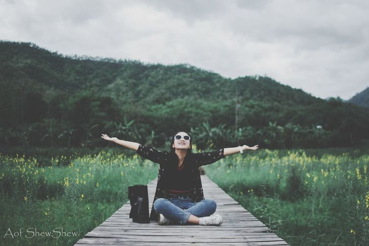 Full length of woman sitting on landscape against sky