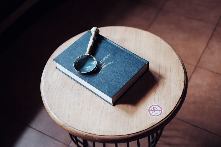 High angle view of book and magnifying glass on table at home