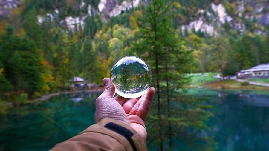 Cropped hand of man holding crystal ball by lake