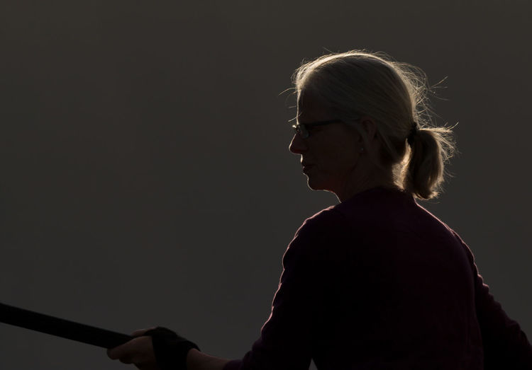 Silhouette Woman Holding Stick While Standing Outdoors