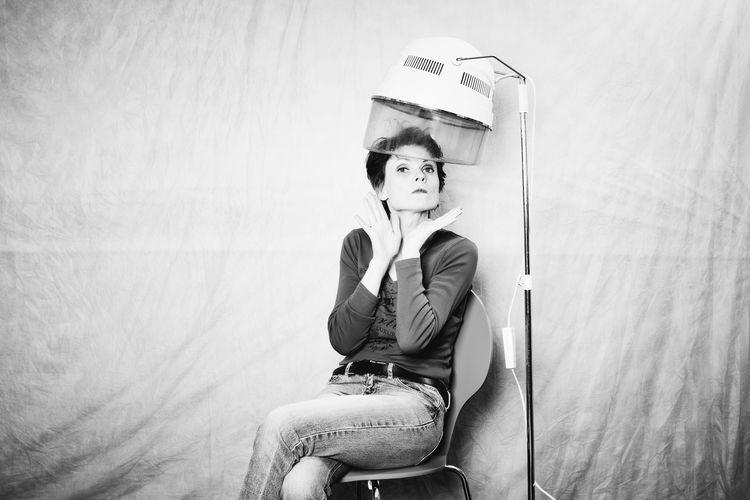 Portrait of woman sitting against curtain