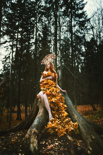 Young woman covered with leaves sitting on tree at forest during autumn