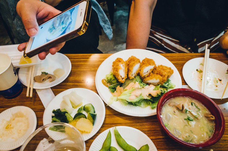 Cropped hand photographing food served at table