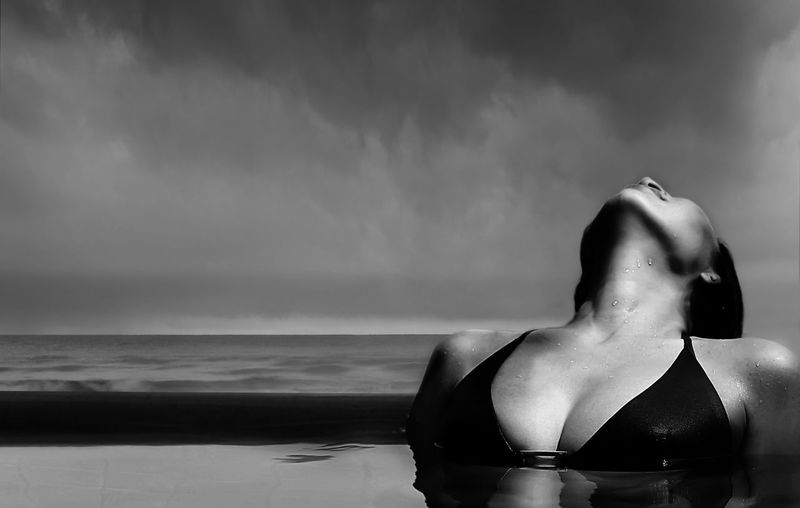 Close-up of sensuous woman in infinity pool against sea