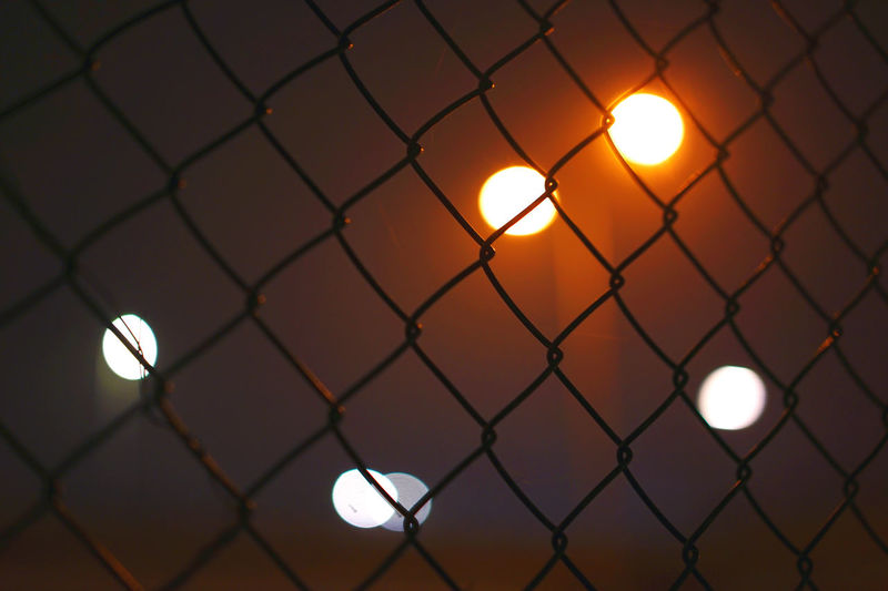 Close-up of illuminated chainlink fence at sunset