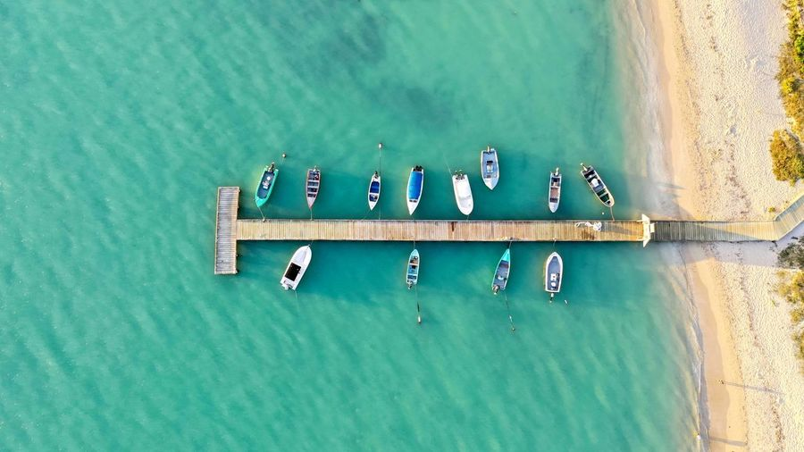 Aerial view of boats moored in sea by pier