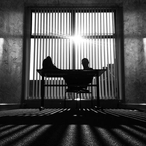 Businessman sitting against window in office