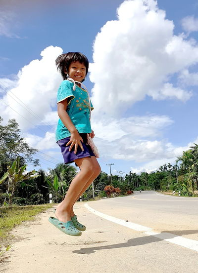 Full length of smiling girl against sky
