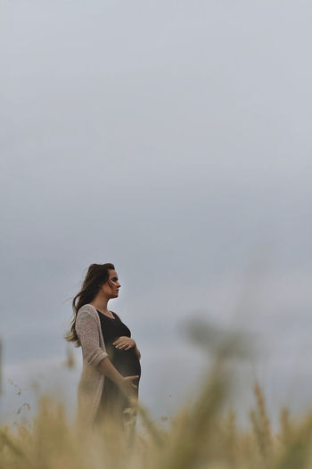 Low angle view of pregnant woman standing against clear sky