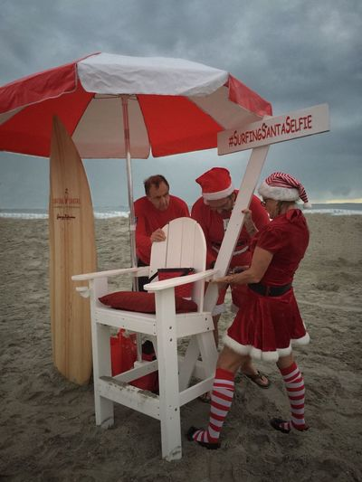 Santa's helpers setting up a selfie stand Surfing Santas Cocoa Beach, Florida Santa's Helper Real People Beach Beach Photography