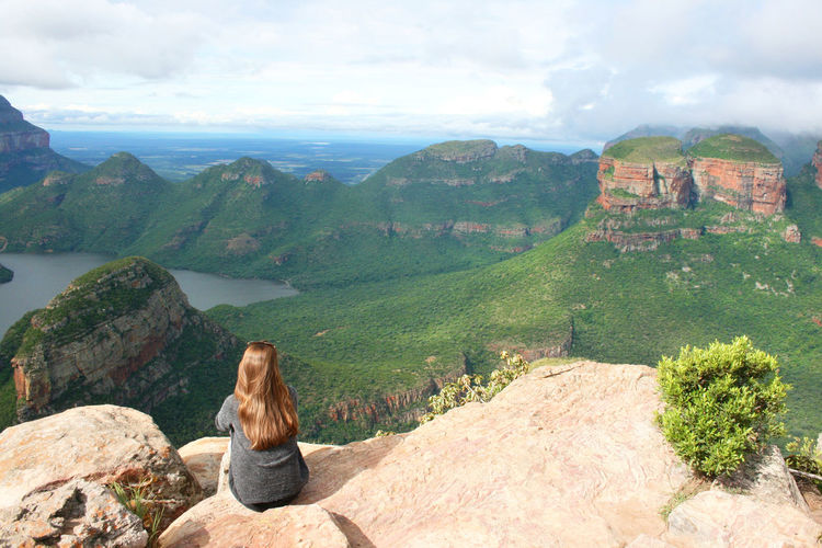 High angle view of woman sitting on cliff against sky