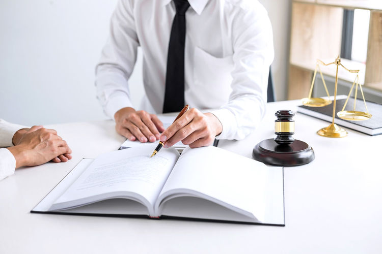 Midsection of judge writing on book while client sitting at table