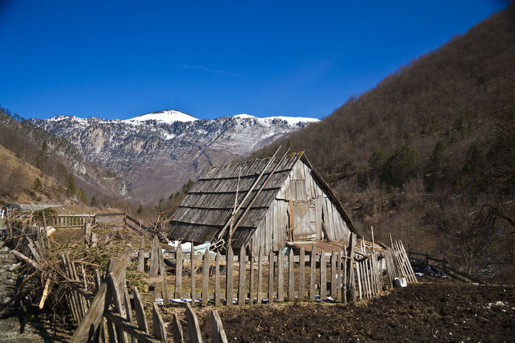 Old abandoned building by mountains against sky
