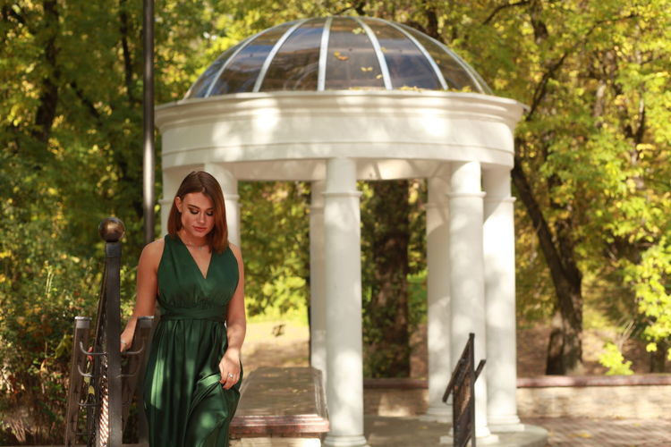 Portrait of smiling woman in green silk dress standing against autumn park
