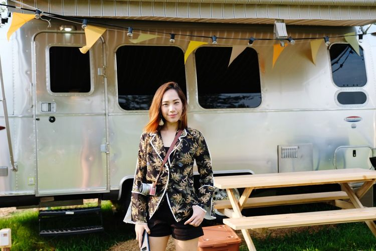 Portrait of young woman standing by motor home