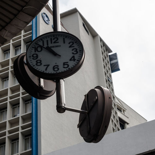 Low angle view of clock hanging on wall