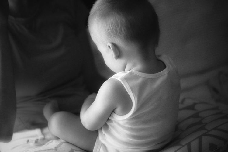 Baby boy sitting on bed in the evening
