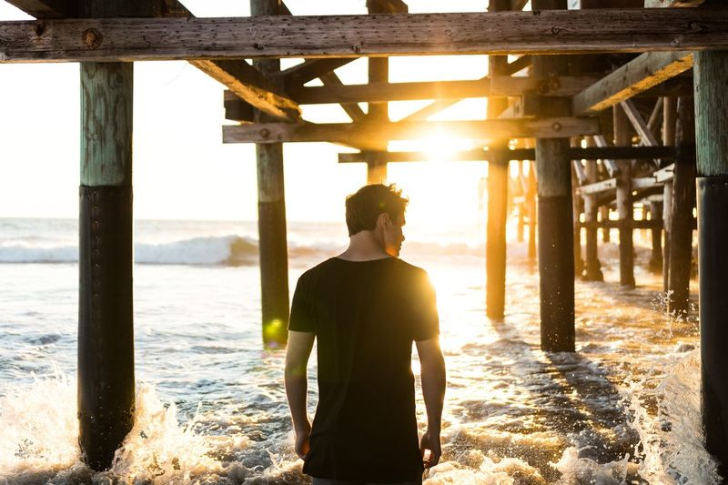 Rear View Of Man Standing Below Pier At Beach