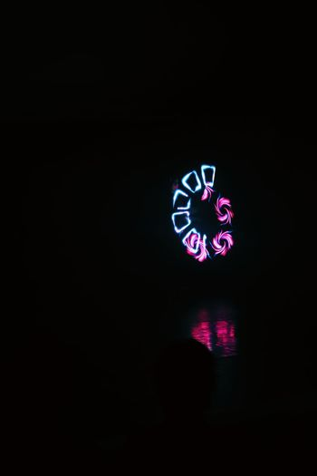 Close-up of illuminated light painting on wall in darkroom