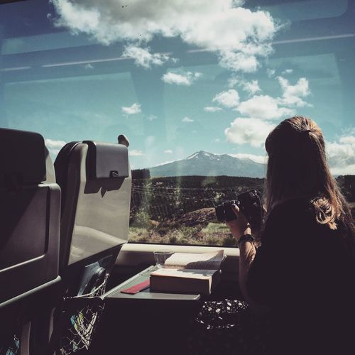 Woman With Camera Sitting In Train While Looking At Mountain