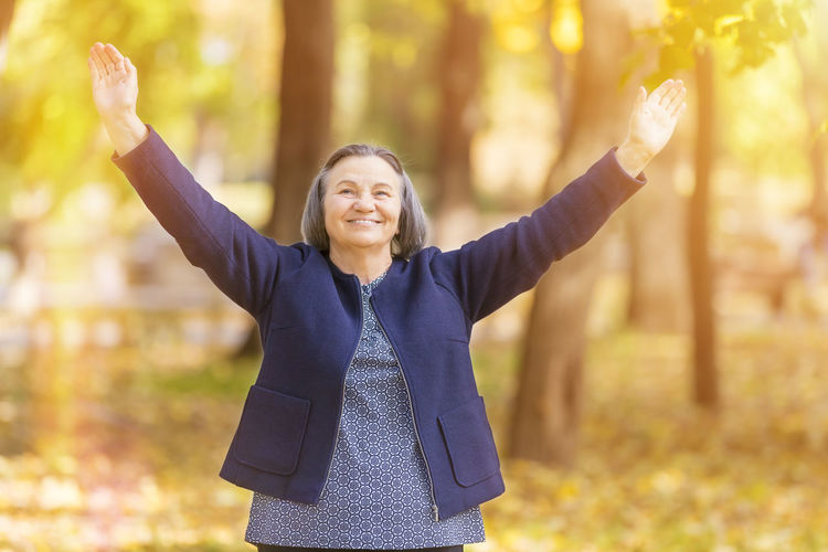 Happy Woman With Arms Outstretched Standing On Land