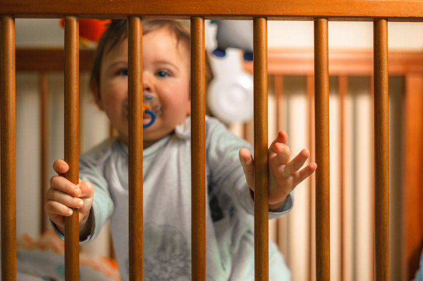 Babyboy Railing Babyhood Bed Bedroom Cage Childhood Close-up Cot Bed Day Dummy Flash Photography Human Hand Indoors  Looking At Camera Pacifier In Mouth Portrait Prison Bars Prisoner Trapped