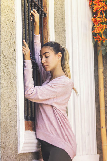Side view of young woman standing against window