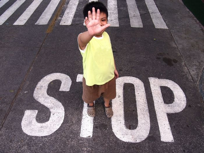 Full length of boy showing stop gesture while standing on road