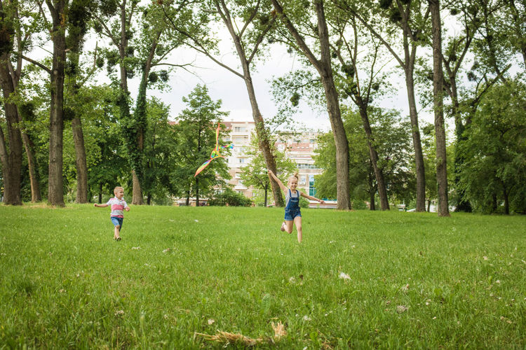 Rear view of children playing on grassy field