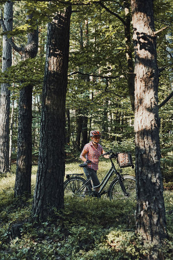 Active woman spending free summer vacation time on a bicycle trip in a forest