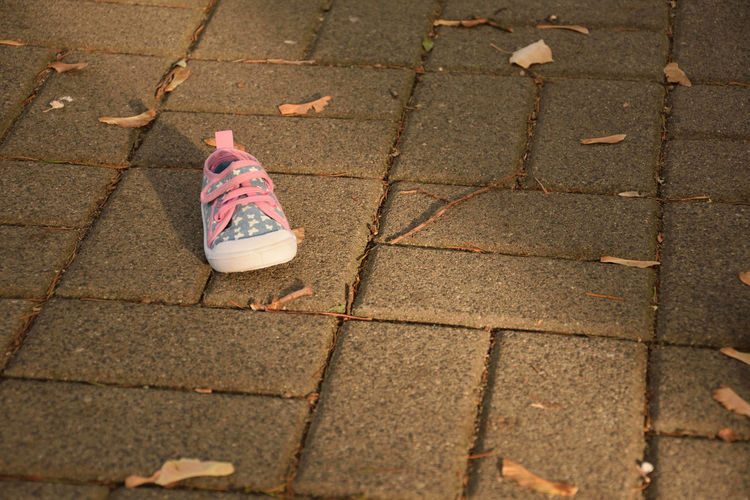 Baby's shoe on the footpath in the park - closeup Small Pattern Close-up Food Pink Color Nature Cobblestone Outdoors High Angle View No People Sidewalk Day Stone City Paving Stone Street Footpath Shoe