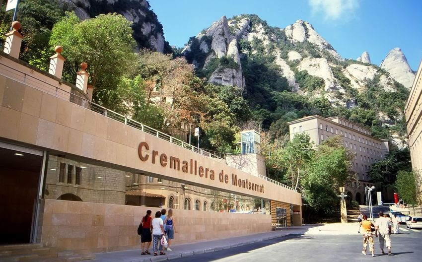 Architecture Building Exterior Built Structure Casual Clothing Cogwheel Railway In Montserrat Mountain -Catalonia Full Length Large Group Of People Leisure Activity Lifestyles Medium Group Of People Men Mountain Person Road Sky Street Tourist Train Station In The Mountains Of Montserrat-Catalonia Transportation Tree Walking