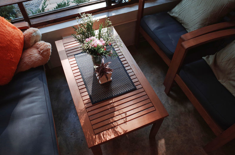 High Angle View Seat Chair Flower Flowering Plant Plant Indoors  Table Lifestyles Wood - Material Day One Person Human Body Part Leisure Activity Furniture Real People Potted Plant Home Interior Pillow