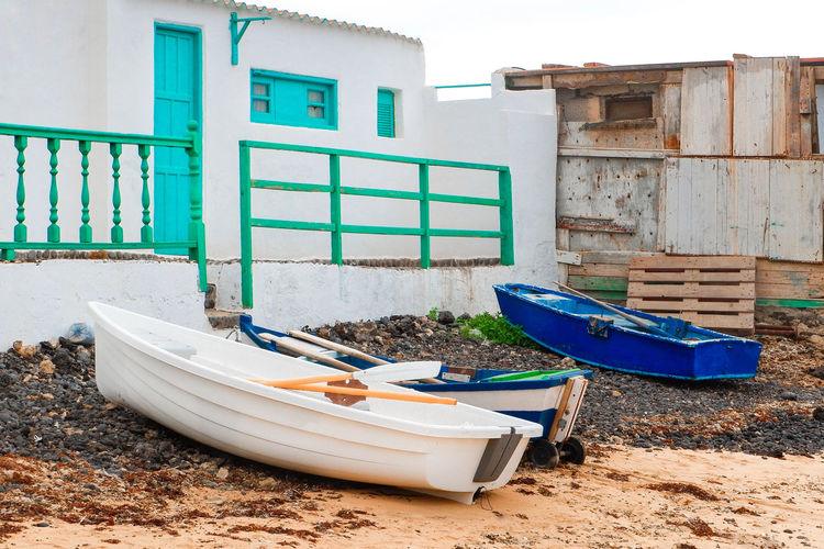 Boats moored on shore against buildings