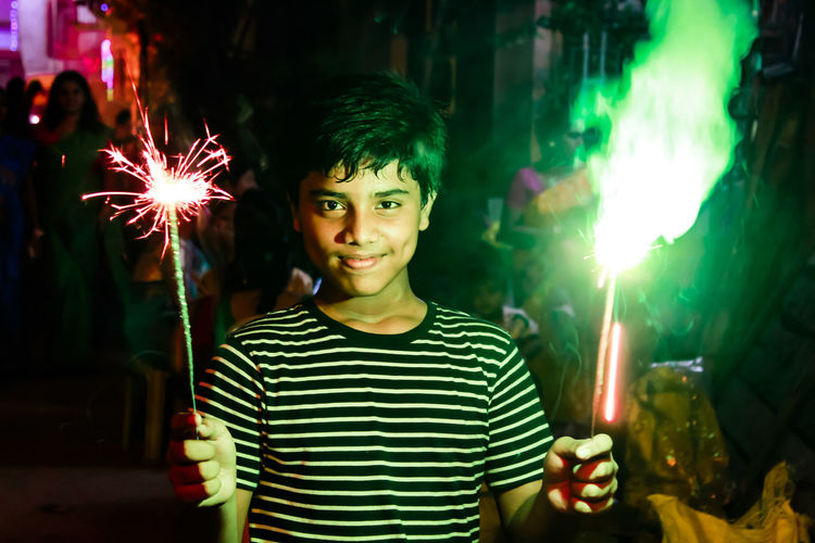 Portrait of teenage boy holding sparklers at night
