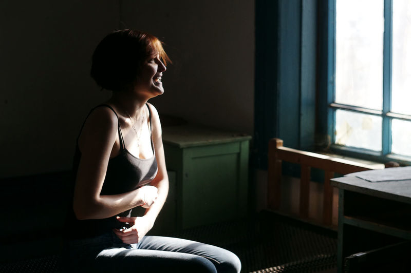 Young woman sitting in window