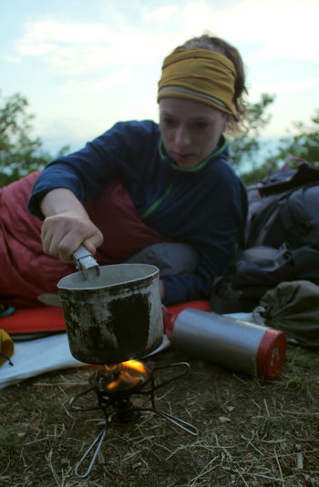 female hiker cooking outdoors Backpacking Camping Cooking At Home Hiking Hydration Stove Travel Trekking Woman Adventure Backpack Bonfire Burning Campfire Caucasian Cup Day Female Fire Fire - Natural Phenomenon Flame Focus On Foreground Food Food And Drink Gas Stove Heat - Temperature Hobby Land Leisure Activity Lifestyles Mature Men Men Mountain Nature Nutrition One Person Outdoors People person Pot Preparation  Preparing Food Real People Relaxation Sitting Sleeping Bag