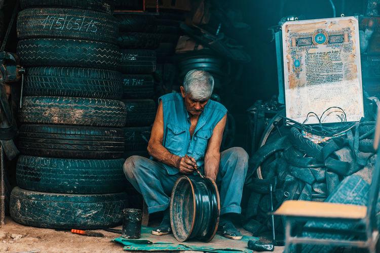 Man working while sitting at garage