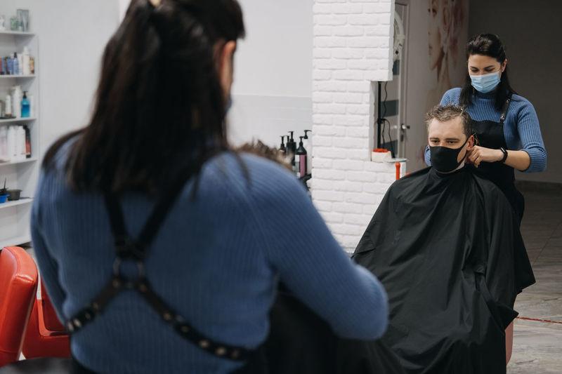 Female barber wearing mask cutting hair of customer