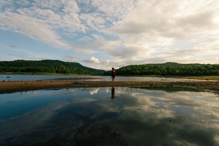Reflection of woman standing on water against sky