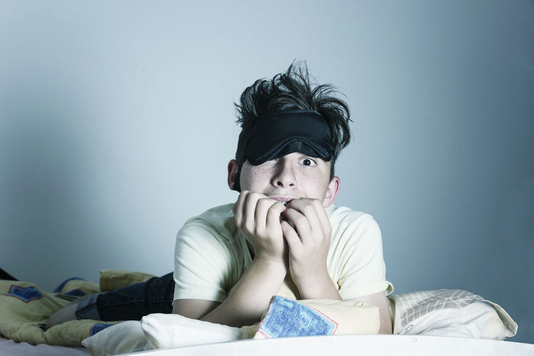 Portrait of teenage boy on bed