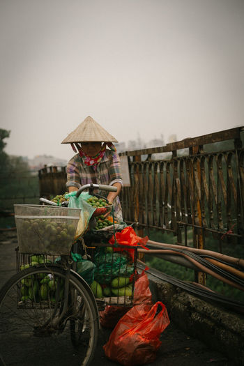Sales woman in Ha Noi, Vietnam ASIA Asian  Asian Style Conical Hat Bag Bicycle Bridge Clouds Day Fruits Hanoi Morning Old One Person Outdoors People Real People Rudimental  Rudimental Alarm Sale Sky Sunrise Transportation Vietnam Water Woman