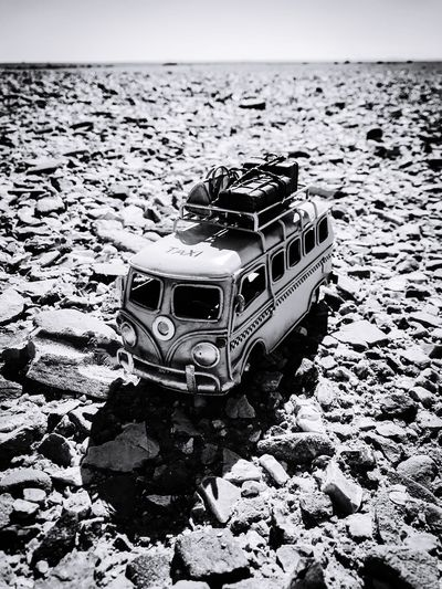 Taxi van (toy) in the erg (desert of rocks), Sultanate of Oman 🇴🇲 Wanderlust IPhone IPhoneography Remote Trip Destination Stones Blackandwhite Oman Desert Travel Destinations Camper Rv Toy Vehicle Bus Taxi Travel