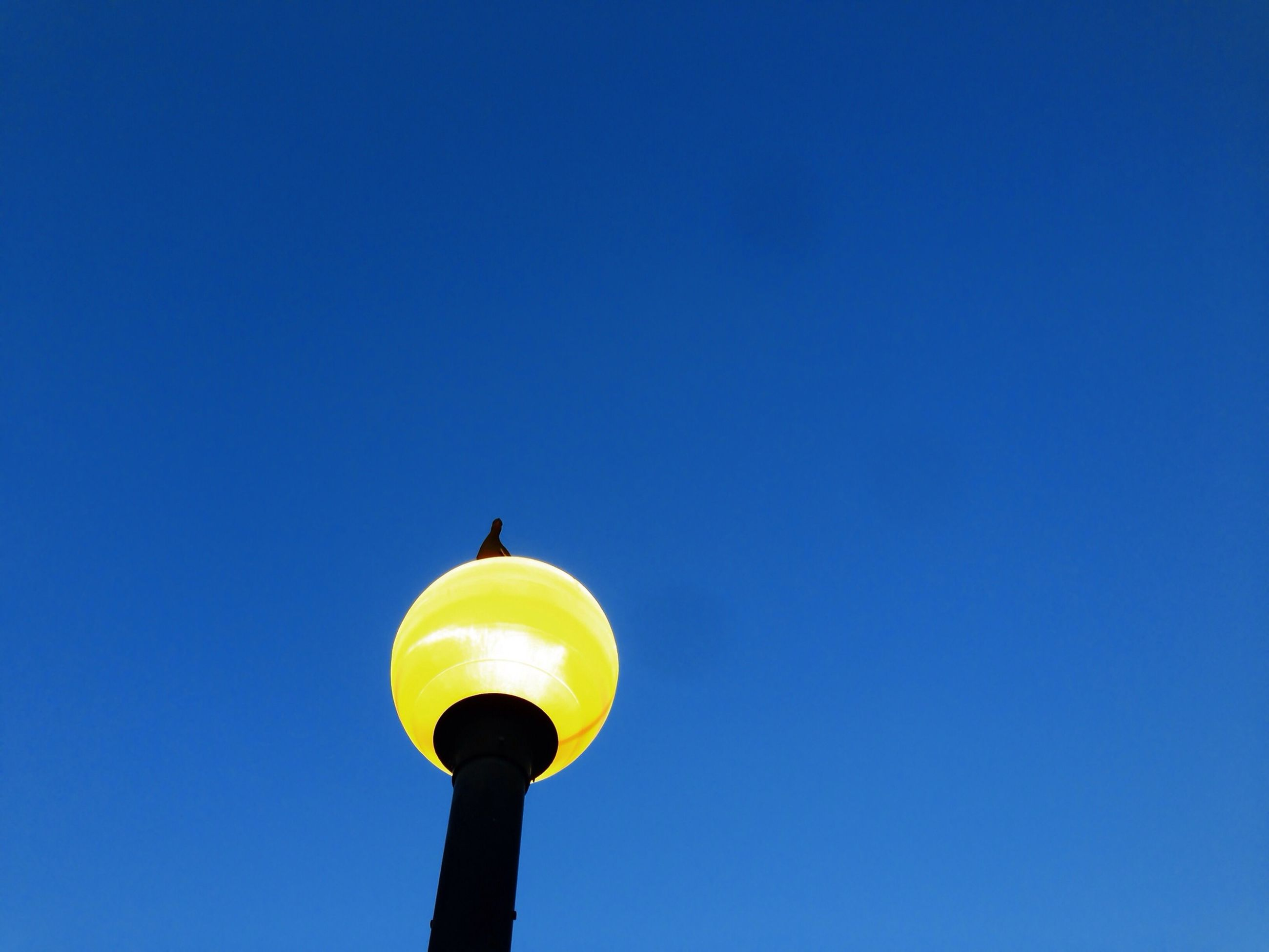 clear sky, copy space, low angle view, lighting equipment, street light, blue, built structure, architecture, illuminated, building exterior, yellow, communications tower, sphere, tower, electric light, high section, lamp post, outdoors, guidance, no people
