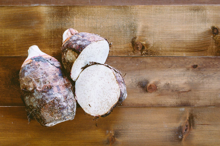 Taro root on wooden background Baked Bread Brown Close-up Cutting Board Directly Above Food Food And Drink Freshness Healthy Eating High Angle View Indoors  Meat No People Preparation  Raw Food Still Life Table Taro Root Temptation Wellbeing Wood - Material